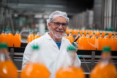 Factory engineer standing near production line with walkie talkie