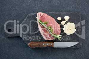Sirloin chop, knife and garlic on slate plate