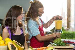 Shop assistant preparing juice at health grocery shop