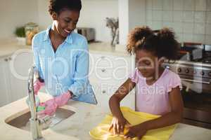 Mother assisting her daughter in cleaning utensils