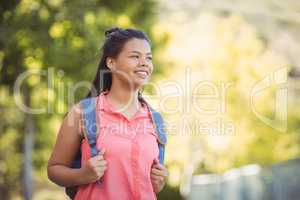 Smiling schoolgirl standing with schoolbag in campus