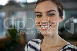 Smiling female executive standing in creative office