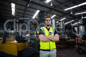 Portrait of factory worker standing with arms crossed