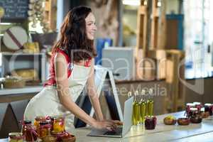 Female shop assistant using laptop at the counter