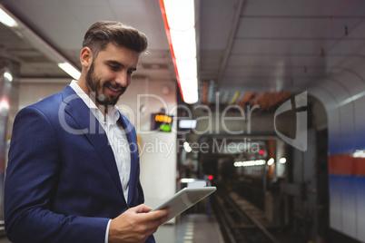Executive using digital tablet on platform