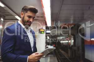 Executive using digital tablet on platform