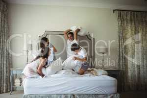 Parents and kids having pillow fight on bed