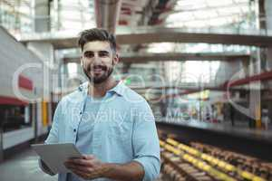 Smiling executive using digital tablet on platform