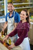 Shop assistants arranging jam and pickle jars at grocery shop
