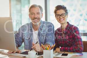 Portrait of male graphic designer sitting with coworker in office