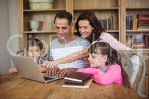 Parents and kids using laptop on table in study room