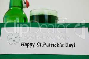 Mug of green beer and beer bottle for St Patricks Day