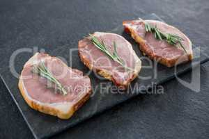 Sirloin chops and rosemary herb on slate plate