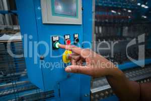Hands of factory worker pressing a green button on the control board