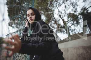 Anxious teenage girl leaning on wire mesh fence at school campus