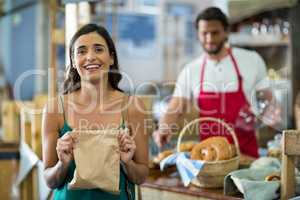 Portrait of smiling female customer showing parcel bag at counter
