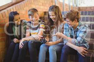 Smiling school students sitting on the staircase using mobile phone