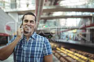 Executive talking on mobile phone on platform