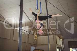 Female gymnast practicing gymnastics on rings