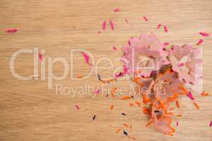 Colored pencils shavings on a wooden background