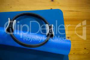Pilates ring and exercise mat kept on wooden floor
