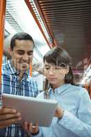 Executives using digital tablet travelling in train
