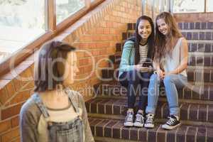 School friends bullying a sad girl in school corridor