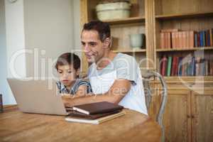 Father and son using laptop in study room
