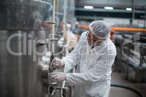 Factory engineer turning control wheel of storage tank