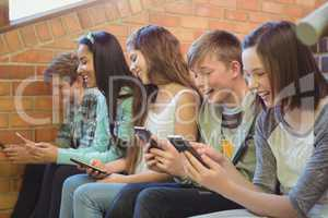 Group of smiling school friends sitting on staircase using mobile phone