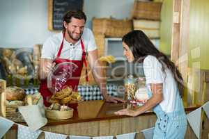 Bakery staff showing snack to the female customer at counter