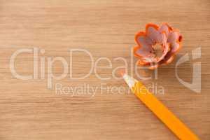 Close-up of orange color pencil with pencil shaving