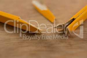 Broken yellow pencil on wooden background