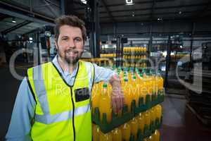 Portrait of factory worker leaning on packed orange juice bottles crate