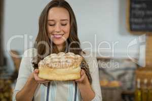 Smiling female staff holding round loaf of bread at counter