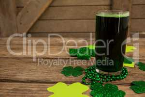 Glass of green beer, beads and shamrock for St Patricks Day