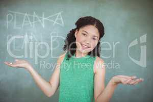 Portrait of schoolgirl gesturing while pretending to be a teacher in classroom