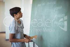 Attentive schoolboy reading chalkboard in classroom