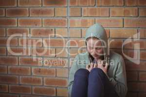 Sad schoolgirl sitting alone against brick wall
