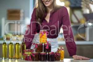 Olive oil, jam, pickle placed together on table