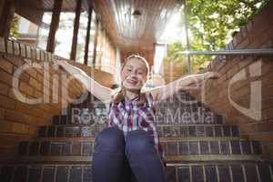 Portrait of happy schoolgirl sitting with arms outstretched on staircase