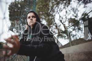 Anxious teenage girl leaning on wire mesh fence