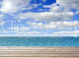 Wooden plank with turquoise sea or ocean and blue sky