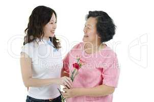 Mother and daughter holding carnation flower and smiling
