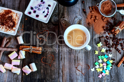 cup of black coffee with a dessert on the gray wooden surface