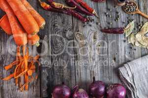 Fresh vegetables carrots and onions on a wooden surface
