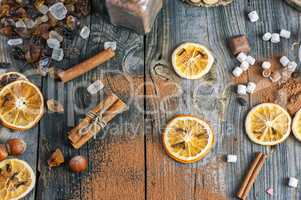 Dried slices of orange and cocoa powder on a gray wooden surface