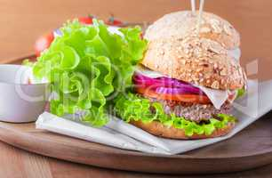 Cheeseburger with salad, onion tomato and fresh bread.