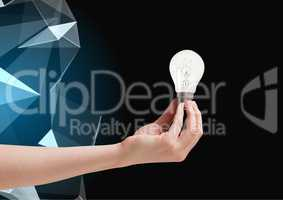 Composite image of Hand holding Lightbulb against graphic polygon in background