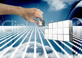 Composite image of Hand holding futuristic blocks against sky